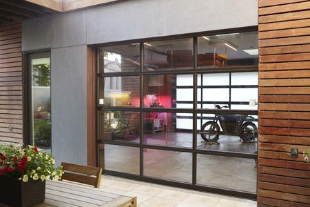The Museum of Science and Industry Chicago Smart Home featured a Clopay Avante with bronze anodized aluminum frame with white laminated glass for the traditional garage door application