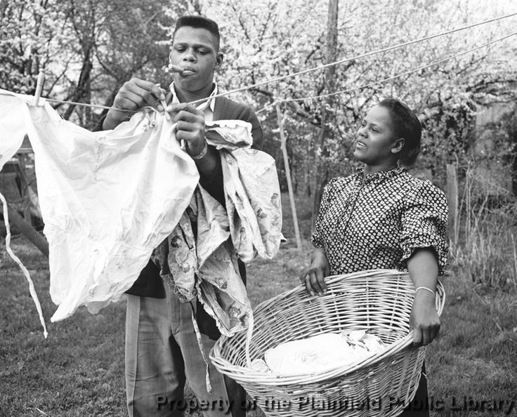 Photo of Milton Gray Campbell helping his mother hang clothes. He was an American decathlete of the 1950s. In 1956, he became the first African American to win the gold medal in the decathlon of the Summer Olympic Games.  Born: December 9, 1933 Died: November 2, 2012