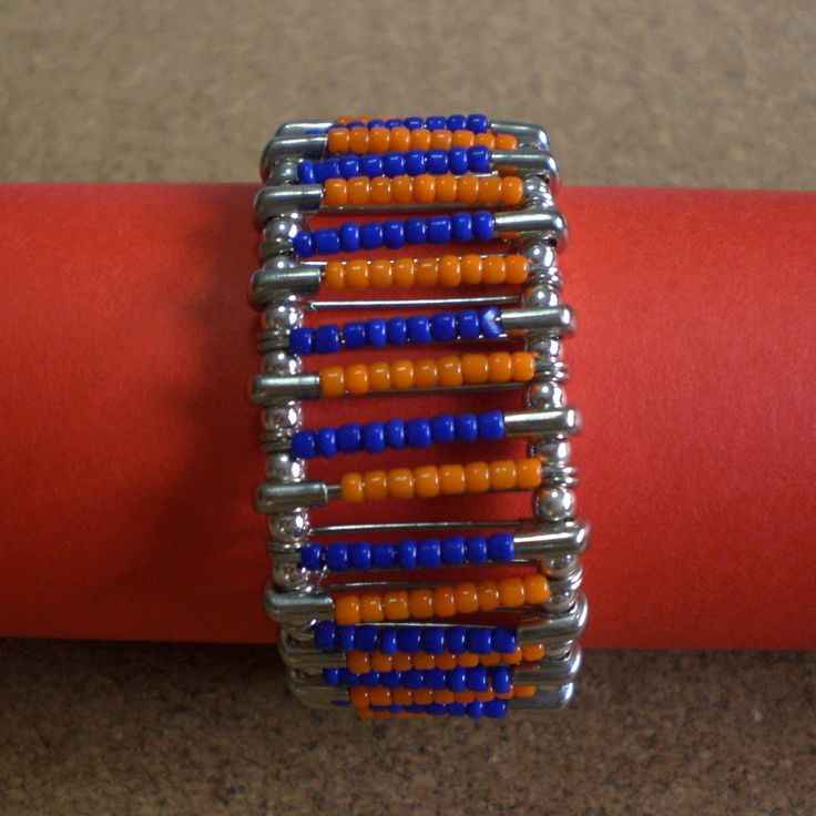 Bracelet made using safety pins with blue and orange plastic beads. Connected with silver round beads.