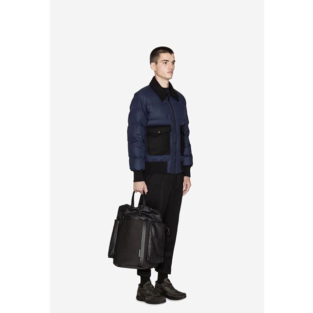 Don't wear black and navy together. This fashion rule still has its fair share of subscribers, but like every other fashion myth is best ignored. Here, the Saar Waxed Canvas rucksack from côte&ciel is teamed with a simple quilted jacket in deep navy and charcoal grey sneakers.