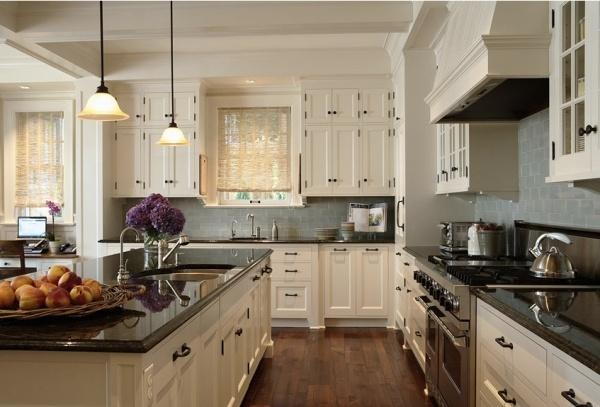 Dream kitchen combination - dark granite, creamy cabinets, dark hardwood, black fixtures, stainless appliances, and blue/grey subway tile