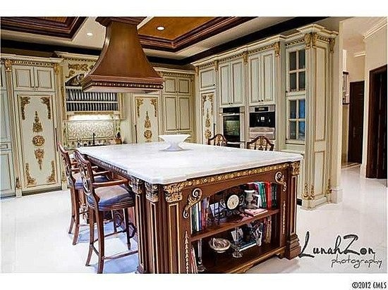 This Bachelorette Pad in NC Kitchen has Miele Appliances! Does any one see the cooktop under the island hood? Probably need different angle. Miele double oven, coffee maker, coffe cup warming drawers and all refrigerator all freezer behind the very ornate panels between the plate rack. Who's thinking Liberace....