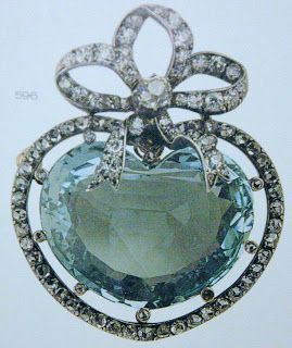 A heart-shaped aquamarine brooch by Faberge, which is nicely topped by a diamond bow and a border of diamonds.
