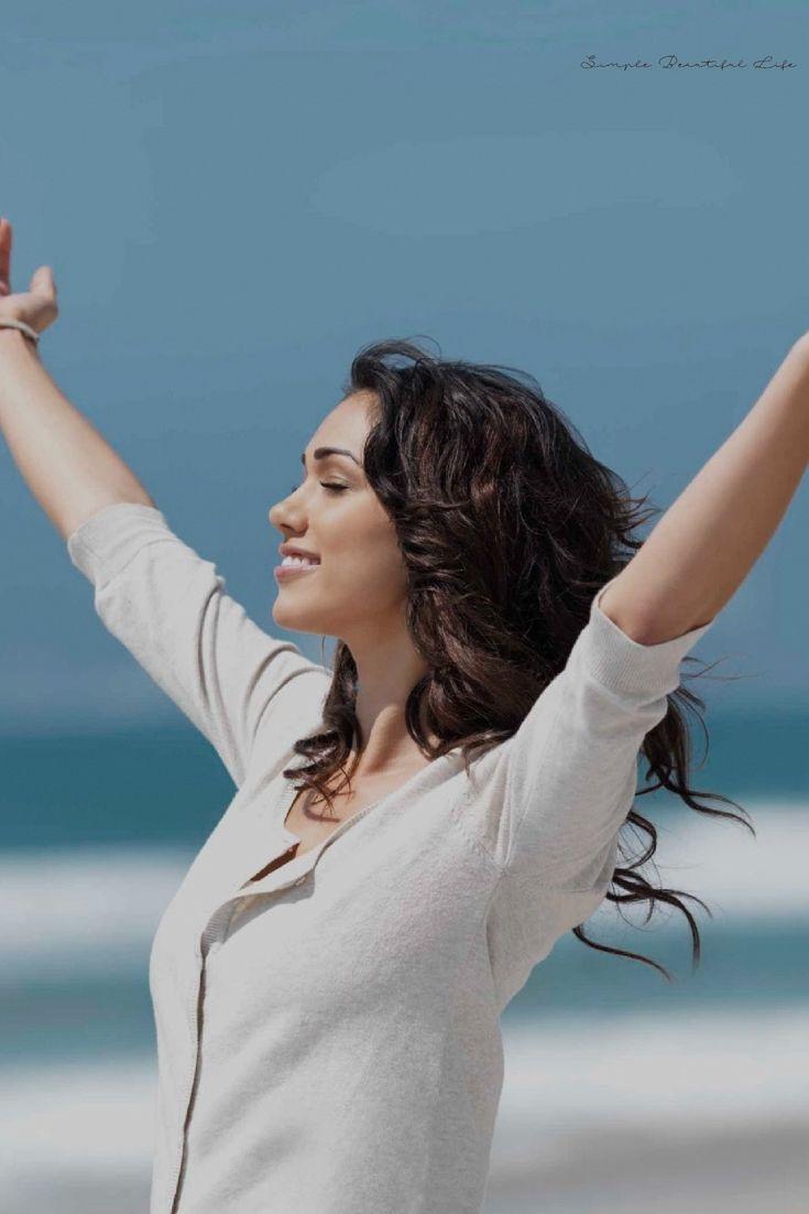 woman raising hands on beach