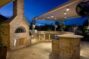 Outdoor Kitchen with grill, deep fryer, refrigerator & ice maker, sink, and a wood-fired pizza oven.