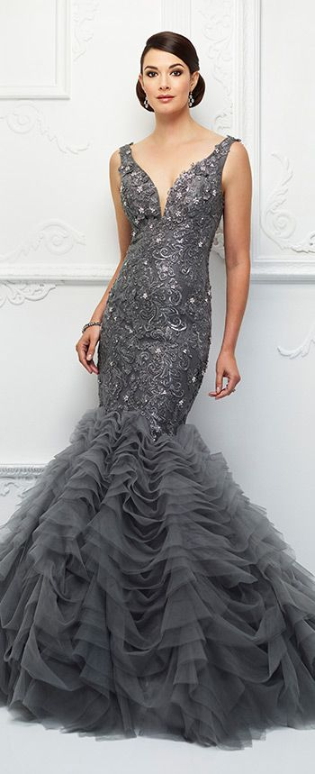 A nod to glamorous Old Hollywood, this sleeveless hand-beaded metallic lace and tulle trumpet gown offers a plunging curved V-neckline with an illusion modesty panel, a beaded lace dropped waist bodice with three-dimensional trim, a V-back, and a dramatic tiered tulle ruffled full skirt with a sweep train. A matching shawl is included.