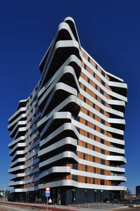 The irregularly shaped balconies project from each corner of the 13-storey-high tower, which was recently completed by Rotterdam Studio 24H Architecture.