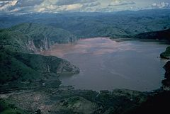 """On a night in 1986, Lake Nyos reached its carbon dioxide saturation point and the lake turned over in an eruption of water that flew 250 ft into the the air. Gas emerged from the lake in that explosion, sweeping over the valleys and, being denser than air, sinking to suffocate the people below. Death came quickly. 1 man said, """"We heard a noise, just like a gunshot."""" He checked on his 2 young daughters and found them dead in their beds. A total of 1,746 people were smothered in the night."""