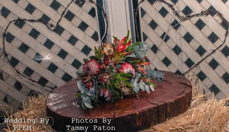 Rustic Barbed wire hearts with native bouquet and a slab of country hard wood resting on a bale of hay simple elegance.