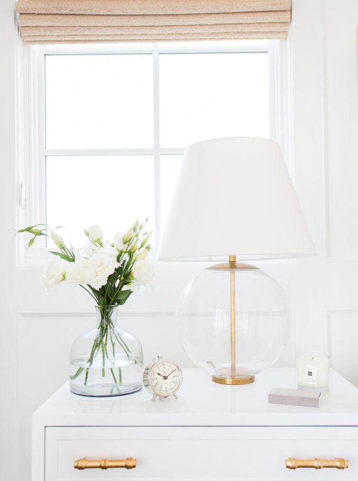 Clear glass table lamp with simple white shade and gold details.