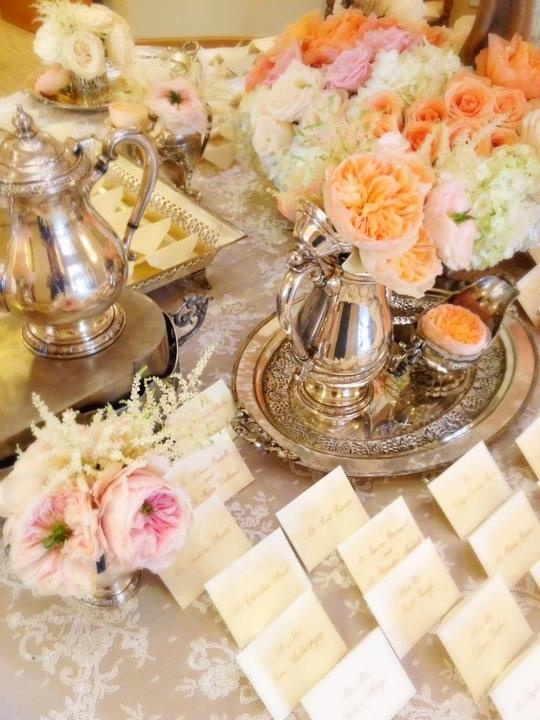 Details Details Wedding and Event Planning  Lovely escort card table by White Lilac filled with soft pink and peach garden roses, antique silver and lace add the perfect vintage touch!