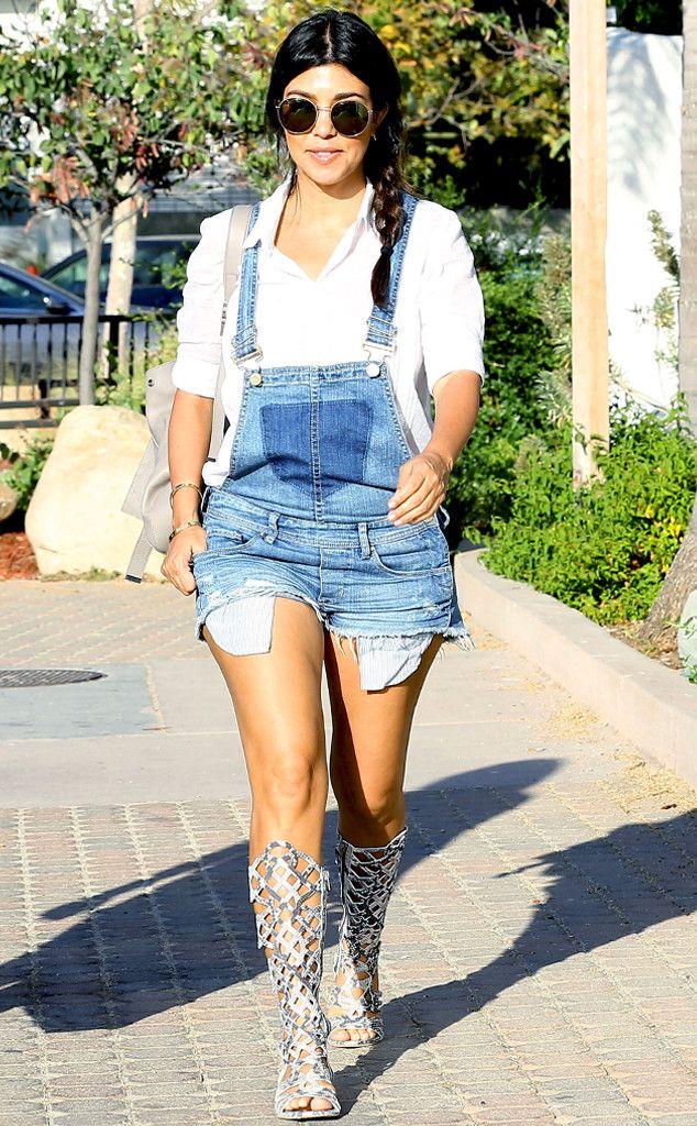 A pregnant Kourtney Kardashian rocks a pair of '90s-style short denim overalls and eye-catching gladiator sandals.