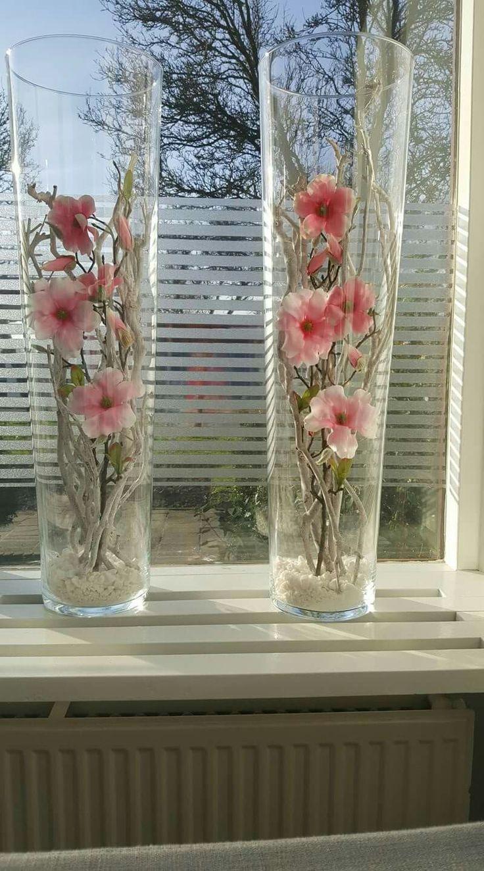 Hoge vazen met takken en bloemen.