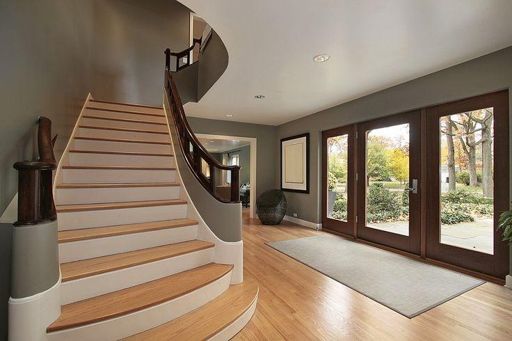 Moderne Empfangshalle mit hellen Holzfußboden und geraden Treppe bis zur Landung.