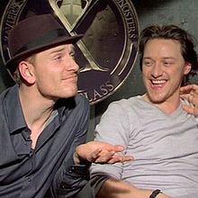 """Michael Fassbender and James McAvoy sit in front of the """"X"""" logo for Xavier's school."""