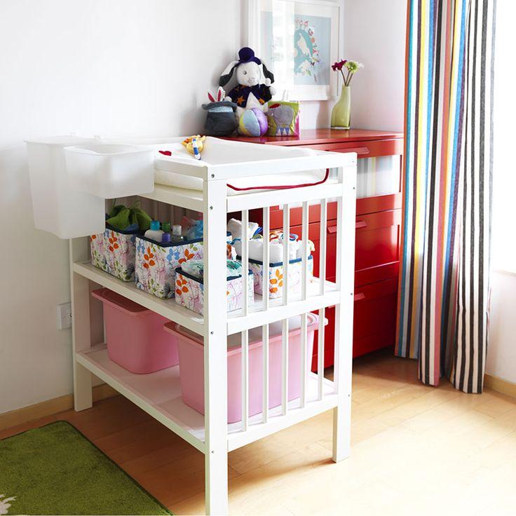 Pokój dziecięcy z białym stołem do przewijania wypełnionym pojemnikami do przechowywania oraz czerwona komoda