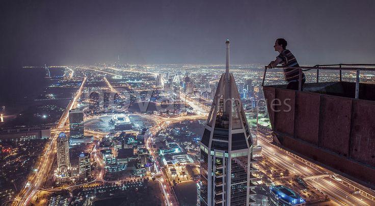 Man looks at Dubai at night