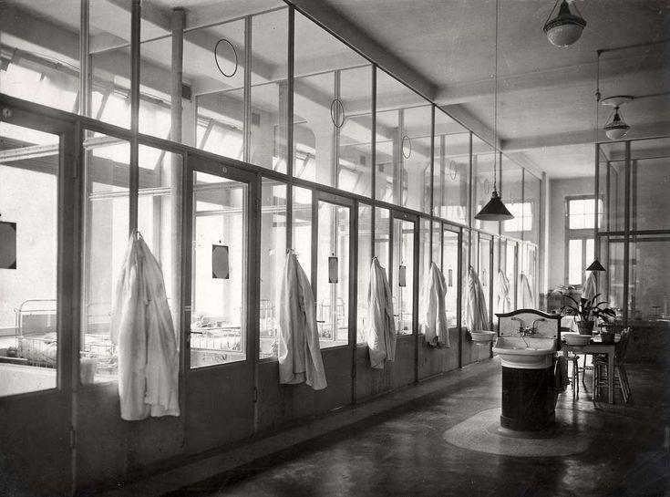 Zaal in de kinderkliniek van het Binnengasthuis te Amsterdam van buiten gezien, met witte jassen op de gang en een wastafel en zithoek. Nederland, 1918.