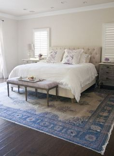 Find peace and comfort in a simple master bedroom with a beautiful antique rug
