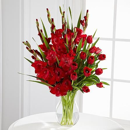 Reflect on your time together with fondness and convey your deepest condolences with a bouquet of glowing red tulips and gladiolus accented with bright greenery in a clear glass vase. A life that was so filled with love should be honored with a beautiful and loving sentiment delivered to the funeral or memorial, or to someone's home. Bouquet sizes are approximate.