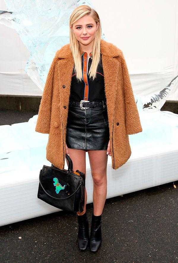 Grace Moretz aposta em mini saia no inverno, complementando com casaco faux fur…