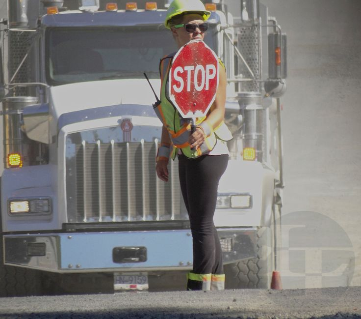 Lollipop Lady stands before a Kenworth truck