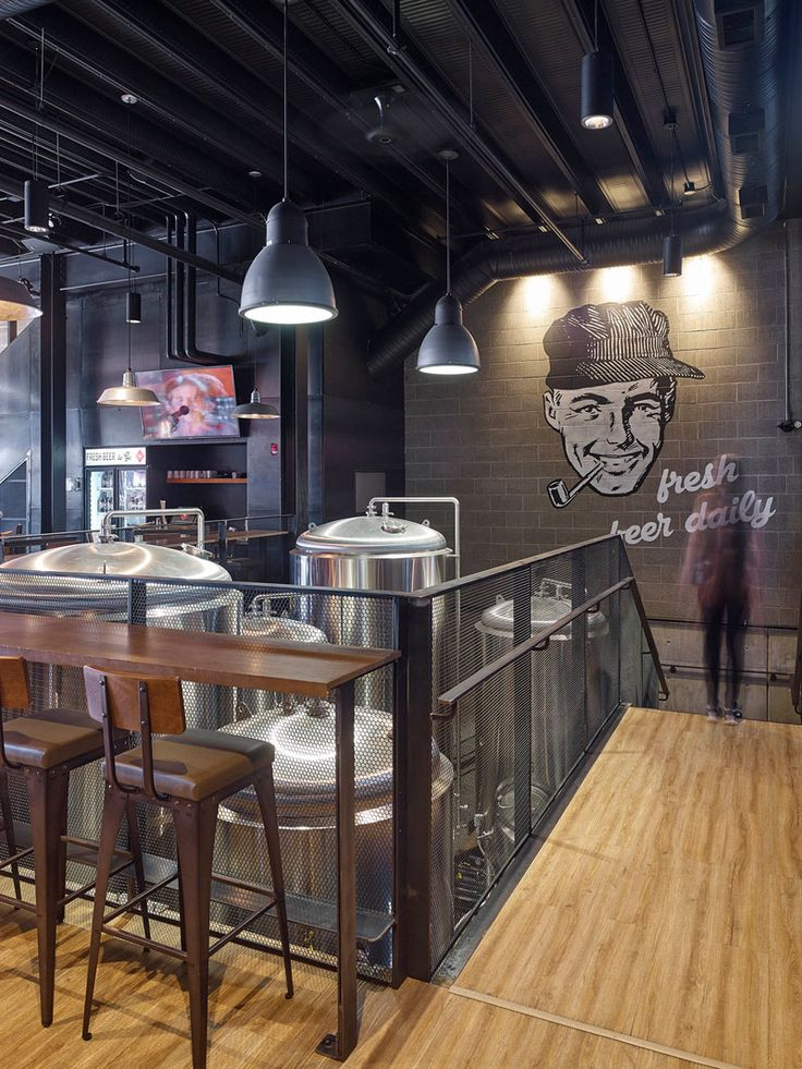This industrial inspired brew pub and restaurant design features a large wall mural and glimpses of the beer making equipment.