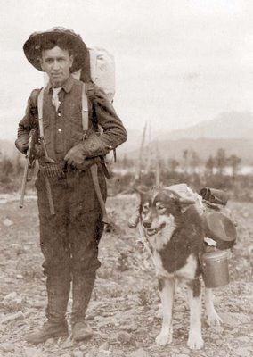 This picture was taken in the early 1900's near Seward, Alaska. It shows a gold prospector and his pack dog. He is preparing to leave for the summer prospecting season. He, and his dog, appear to be well equipped.