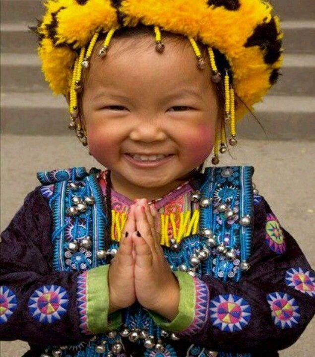 Happy little girl in traditional garb and headdress.