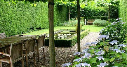 http://www.tuindesign-ten-horn.nl Tuinarchitect - tuinontwerp. Moderne eigentijdse stadstuin met vijver en intiem terras onder dakbomen in Limburg. Groene onderhoudsvriendelijke tuin.