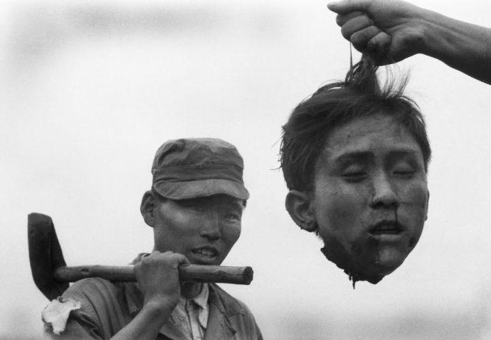 Un policía surcoreano sostiene la cabeza decapitada de un miembro de la guerrilla comunista norcoreana durante la Guerra de Corea, en 1952. La foto es de Margaret Bourke-White.