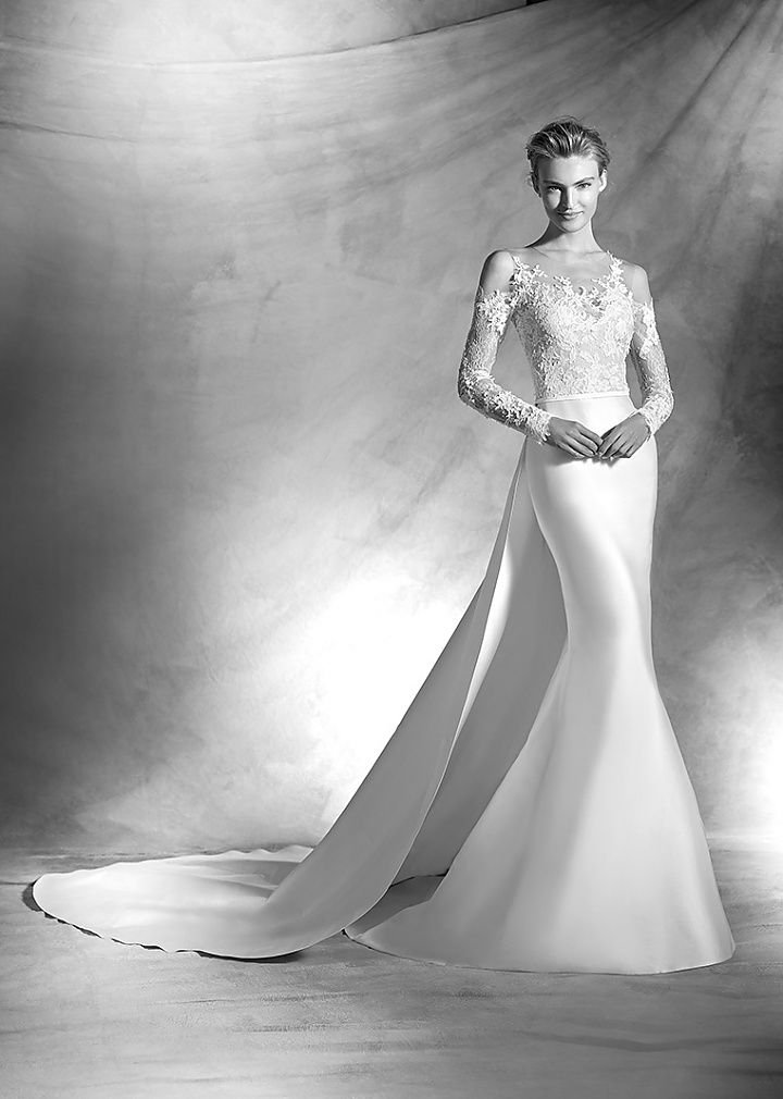 vitorial, collectie 2016 De heldere vorm en lijn van dit trouwkleed is van een ongekende klasse. Voor deze fishtail jurk zijn verschillende materialen gebruikt. Het lijfje met lange mouwen zijn gedeeltelijk  transparant gehouden. Prachtig zoals op de rug, door de off shoulder de schouders en nek uitkomen. De rok loopt vanaf de heup iets wijder uit. Prachtig samen met de gigantische sleep.#zeemeermin #fishtail #exlusief #zijde #glamour #exclusief #atelierpronovias #koonings