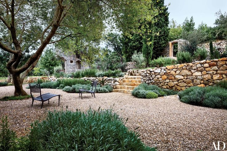 A pair of Sol y Luna chairs from Design Within Reach stand in the garden amid lavender bushes and carob trees | archdigest.com