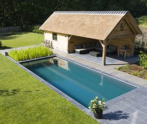 Vanuit de lounge ruimte in deze landelijke houten poolhouse heb je een mooi zicht op het biologisch zwembad.Dit totaalproject werd gerealiseerd door Aqua-Art