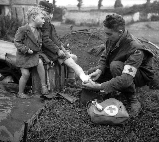 Lance Corporal W.J. Curtis of the Royal Canadian Army Medical Corps, bandaging the burned leg of a French boy, while his young brother looks on. WWII