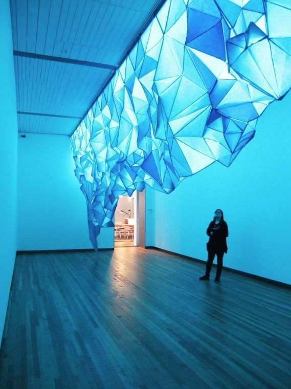 What Lies Beneath by Gabby O'Connor is a striking art installation that looks like an overhanging iceberg. Nevertheless, it will not bring about frosty breaths or frozen fingers because it is not in fact made out of ice. Instead, the illuminating installation has been crafted out of blue-green tissue paper and staples.