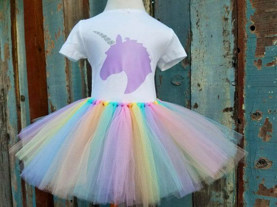 *** RAINBOWS AND UNICORNS Birthday Outfit *** Pieces Are Also Sold Separately! Complete Outfit Includes: - Pastel Rainbow Handmade Tulle Tutu (baby pink, peach, light yellow, mint green, aqua blue & lavender/lilac strips) - Unicorn Top (Lavender/Lilac Vinyl Unicorn Head with Silver Glitter Horn)  THIS LISTING IS FOR SIZES NEWBORN-3T... If you need a larger size, please message me for a custom listing! ...EMBELLISHMENT NOT INCLUDED...  This is a double layered tulle tutu which creates extra…