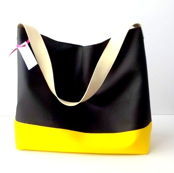 Need a bag thats both spacious and stylish? No problem! This black vegan hobo bag solves busy-day woes with tons of interior storage and a comfortable shoulder strap. Features modern design, black body with yellow bottom topped with an ivory strap. Magnetic snap closure. Fully lined with two internal pockets one is zipped. The material is very soft and durable and easy to clean. Handcrafted in Italy.  Label : Pitti Vintage Handcrafted in Italy One handmade dust cover is included. Size 10.5in…