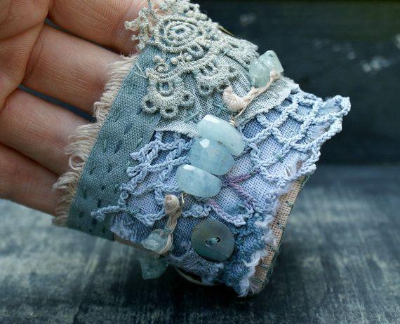 Jai fait ce bracelet manchette de Bohème textile avec des couches de toile de lin, dentelle vintage et le crochet.  Il est orné de magnifiques perles aigue-marine bleus, les trois dans le centre sont assez volumineux et fil sur un fil dargent sterling. Les perles aigue-marine puce sont tressés avec ficelle de linge. Pour une beauté supplémentaire jai cousu quelques boutons de nacre sur le bracelet.  Les couleurs sont Ivoire, beige et bleu de mauvaise humeur.  Sur le tissu de la doublure il y…