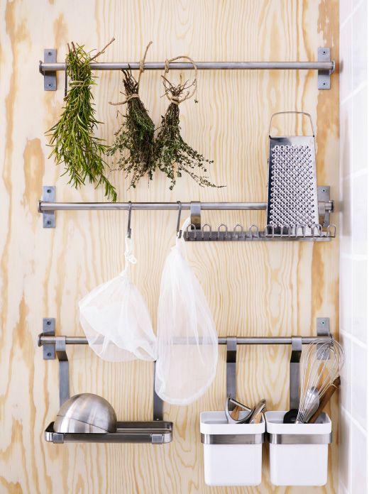 Drie roestvrijstalen IKEA stangen met haken en bakjes met divers keukengerei