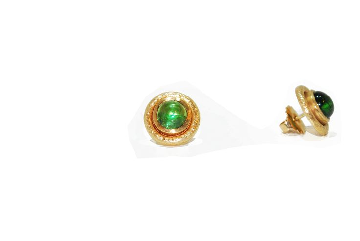 9 ct gold earrings with a spring green tourmaline cabochon in the centre. There is an outer ring of textured pattern which creates a contrast to the polished setting and establishes a beautiful organic form that embellishes the ear.