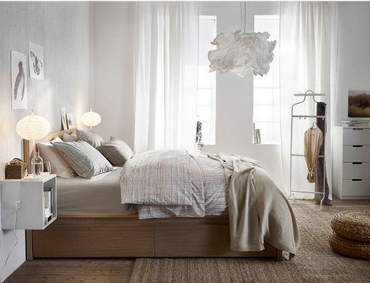 Lyst soveværelse indrettet med en seng af eg med hvid bejdse, en hvid kommode og hvide sengeborde.