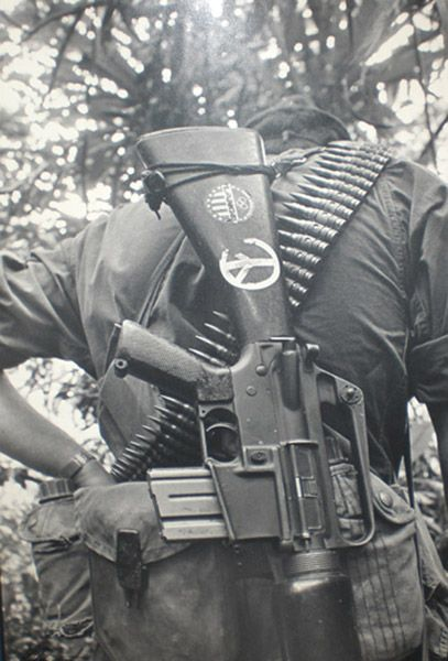Soldier in Vietnam, 1968 - the stock of his gun is painted with a peace sign.