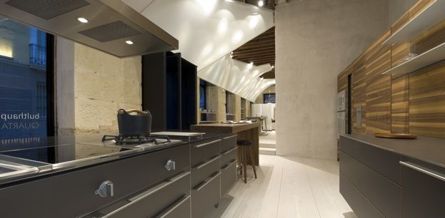 Gray aluminum fronts and wood finish on the walls at bulthaup Quarta in…