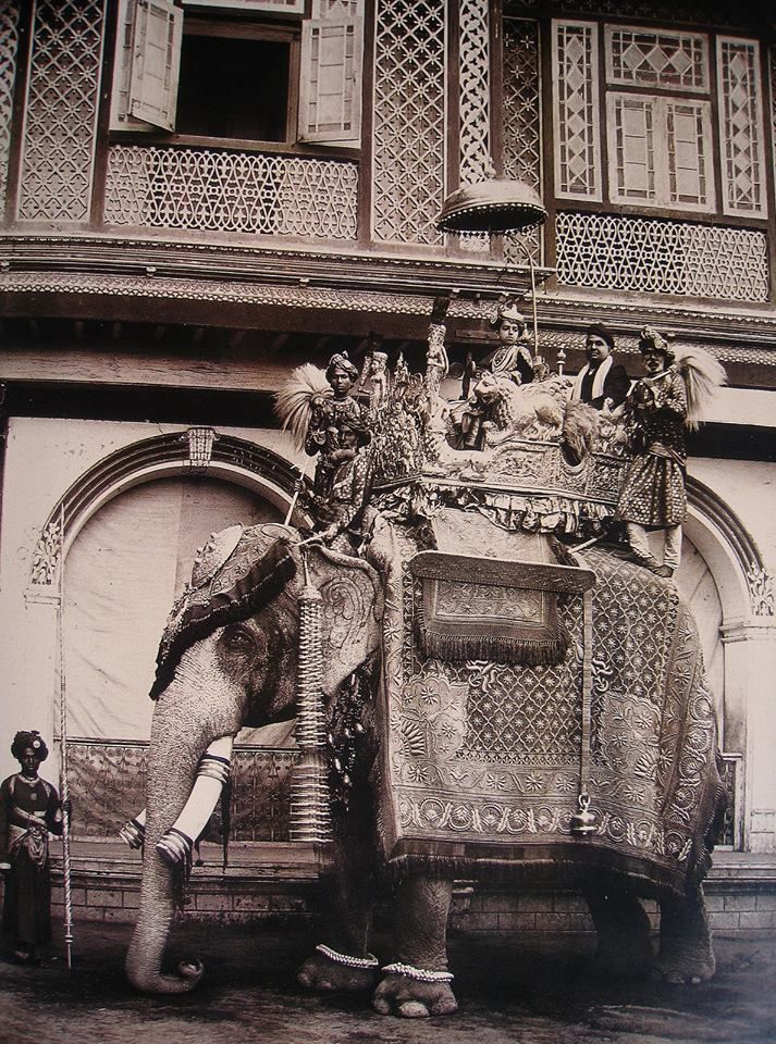 The young Maharajah of Bansda takes a ride on a fabulously-caparisoned royal elephant; take note of the chattra, the umbrella-like canopy suspended above the maharajah's head, and long a symbol of Indian royalty. Via Sacala Regia