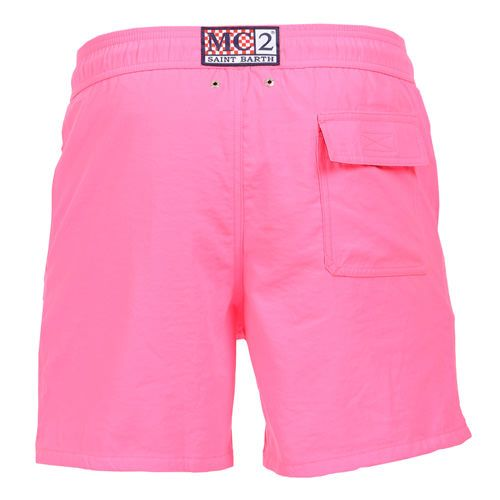 """FLUORESCENT PINK OWNER P SWIM SHORTS WITH SKULLFluorescent pink Long Swim Shorts featuring a skull and """"PIRATES DE SAINT BARTH"""" embroidery at lateral side. Two front pockets and back Velcro pocket. Internal net. Elastic waistband with adjustable drawstring. COMPOSITION: 100% POLYESTER. Model wears size M, he is 189 cm tall and weighs 86 Kg."""