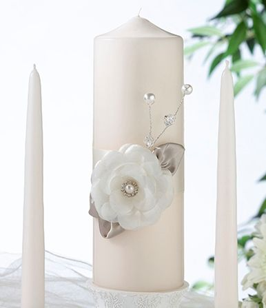 "- This elegant ivory candle set has the style you are looking for.  Decorated with a single large ivory flower with a pearl/rhinestone center, taupe leaves and pearls/crystals .  Set comes with one 9"" pillar and two 10"" tapers."