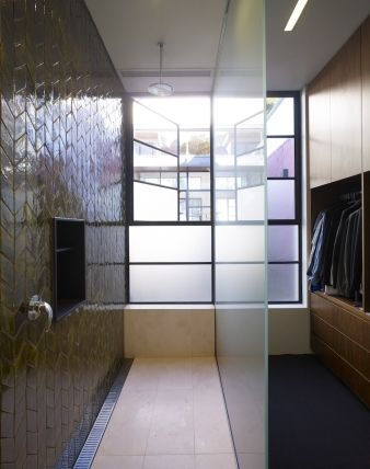 A glass wall separates the shower and wardrobe