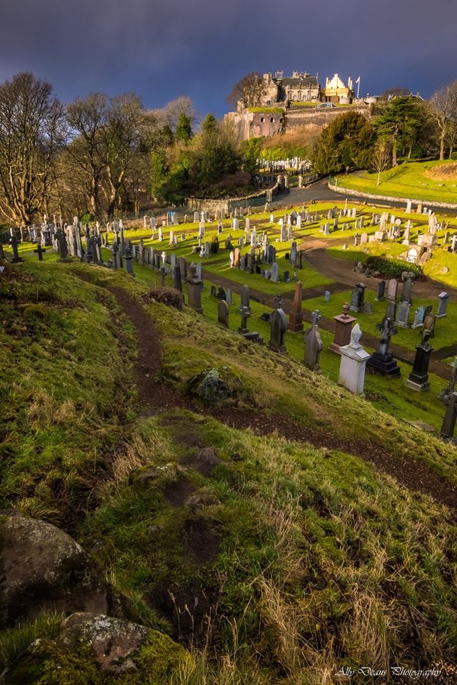 Stirling Castle in sunlight just beyond the graves in Stirling, Scotland.