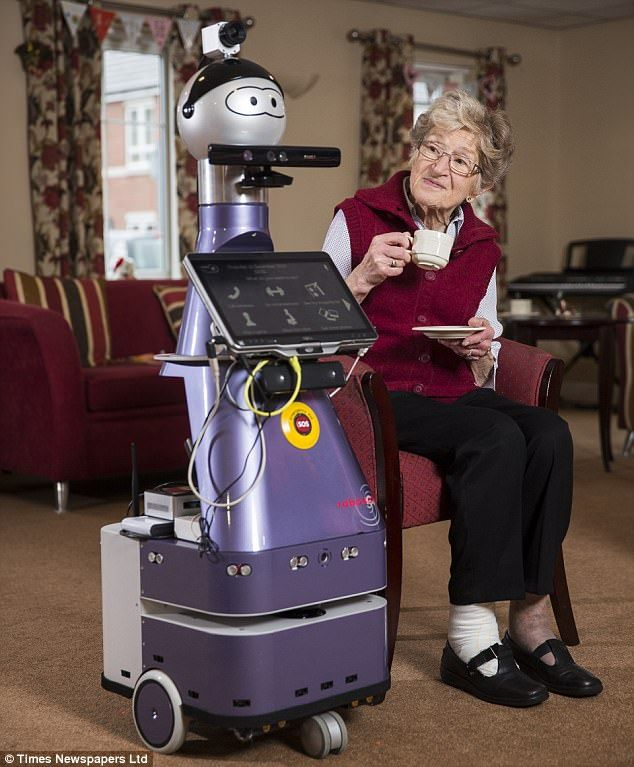Lincoln care home resident Jean Clark, 86, is pictured getting acquainted with a new robot that will be helping to look after her